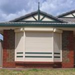 Brick house with white roller shutters