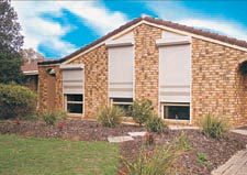 brick home with white roller shutters