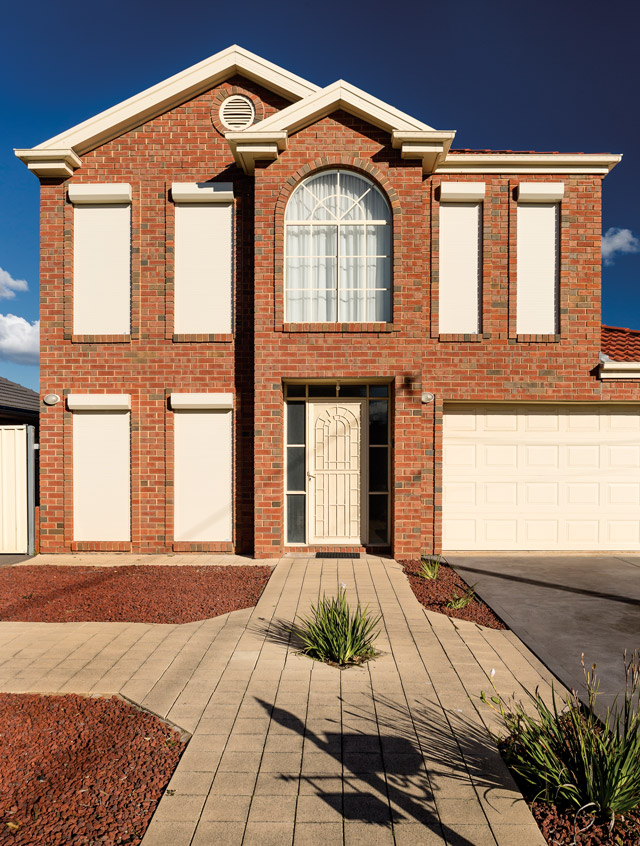 Two storey red brick home with white roller shutters